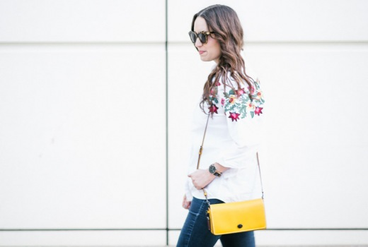 Houston fashion blogger styles embroidered White Button down styled with skinny jeans and the coach dinky bag in yellow.