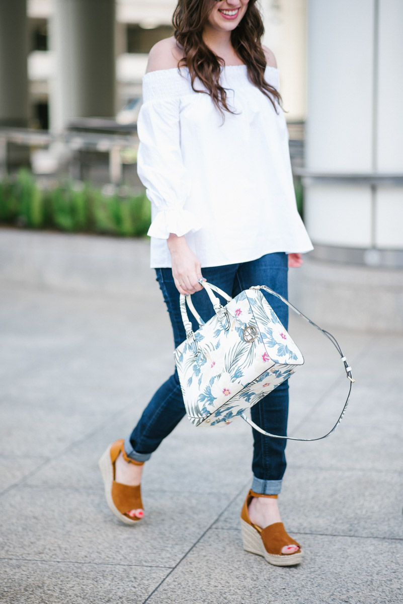 Houston fashion blogger styles a white off the shoulder bow back top with a Henri Bendel floral handbag and Steve Madden wedges for spring outfit inspiration.